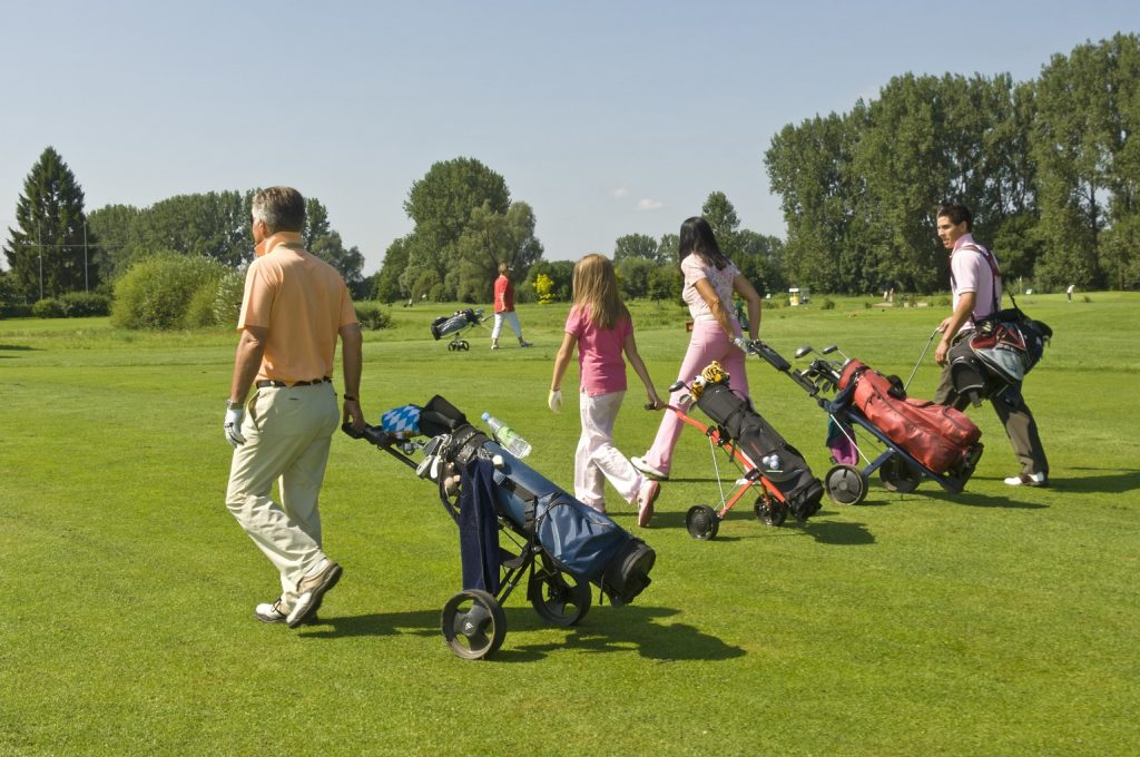 family on golf course carrying golf bags lloydminster hotels